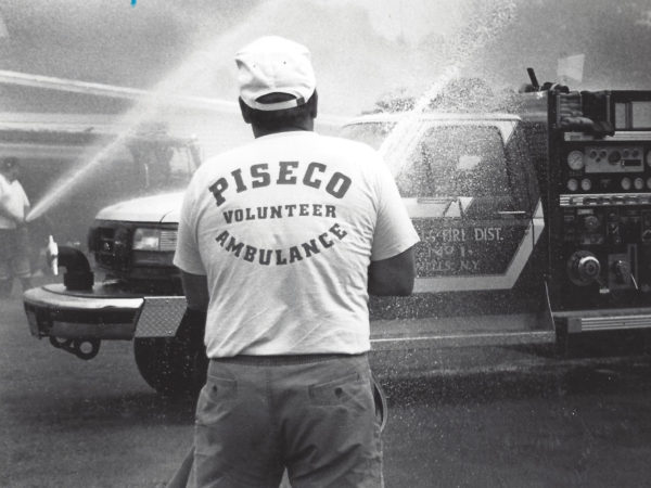 Volunteer sprays fire hose in Piseco