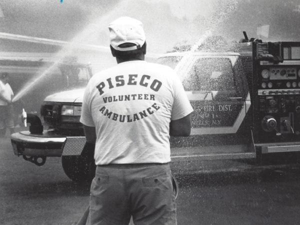 Volunteer sprays fire hose in Piseco