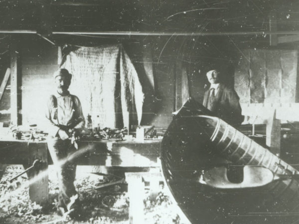 Two men inside the Palmer Boat Shop in the Adirondacks