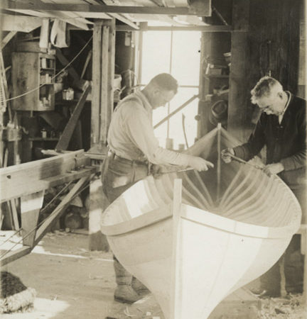 Emerson and worker assemble boat in boat shop in Long Lake