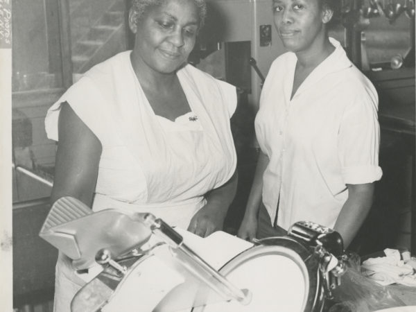 Two women with a meat slicer in the kitchen of the Echo Camp for Girls in Raquette Lake