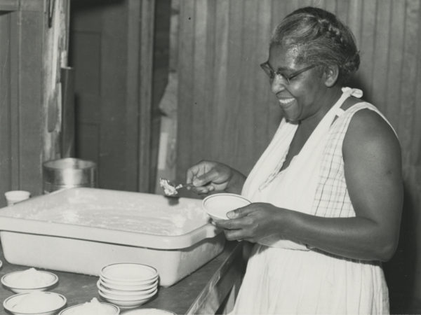 Preparing for a meal in the kitchen of the Echo Camp for Girls. Unidentified African-American cook. Photograph by Edward P. Fynmore of Fynmore Studios. 1950-1970. Raquette Lake, NY. Courtesy of the Adirondack Experience