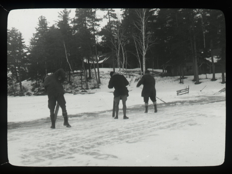 Men cut ice from frozen lake in the Adirondacks
