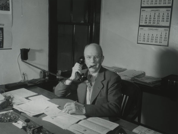 Arthur Owens answers the phone in the office of the Emporium Lumber Company in Conifer