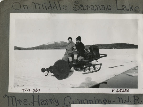 Mrs. Harry Cummings and Noah John Rondeau on motorized ice saw in Saranac Lake