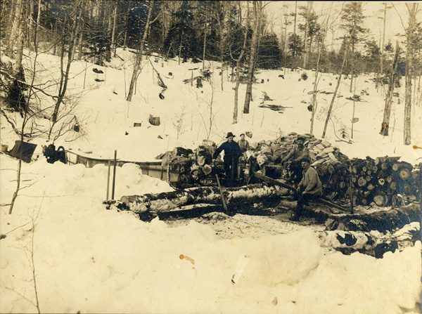 Men cut logs with a crosscut saw during the winter in Big Moose