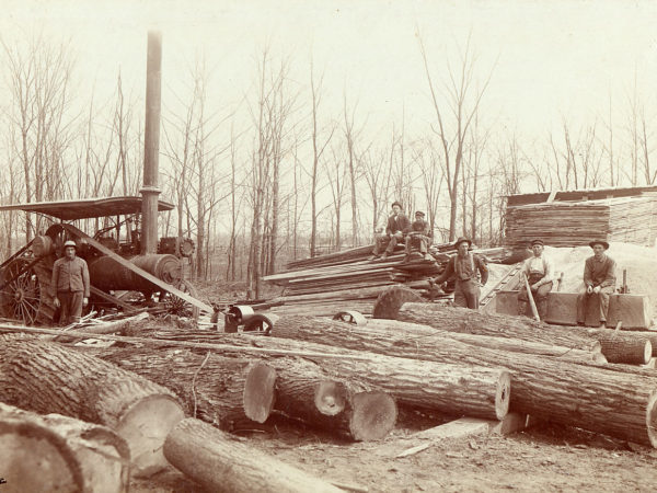 Loggers with steam powered portable sawmill and lumber stacks in the Adirondacks