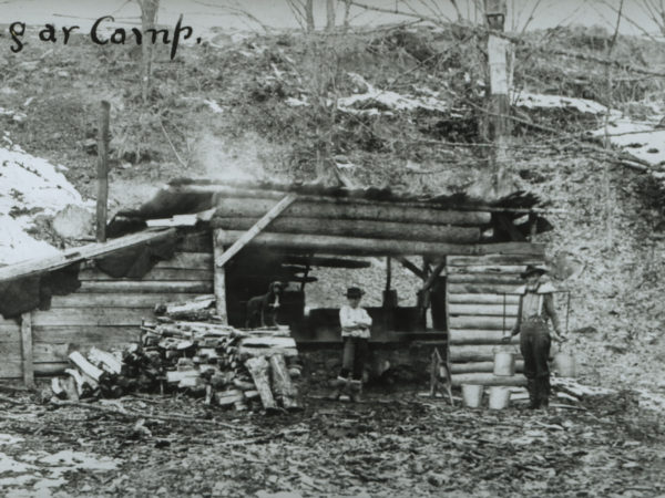 Man holding sap buckets with a yoke at sugar camp in North Creek