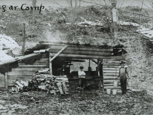 Man holding sap buckets with a yoke at sugar camp in North Creek