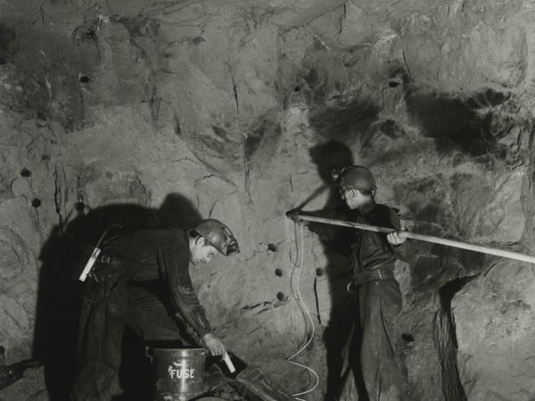 Men load a drift heading with explosives in a mineshaft in Mineville