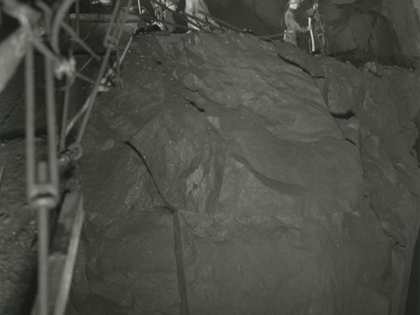 Miners working on a ledge inside a shaft in Mineville