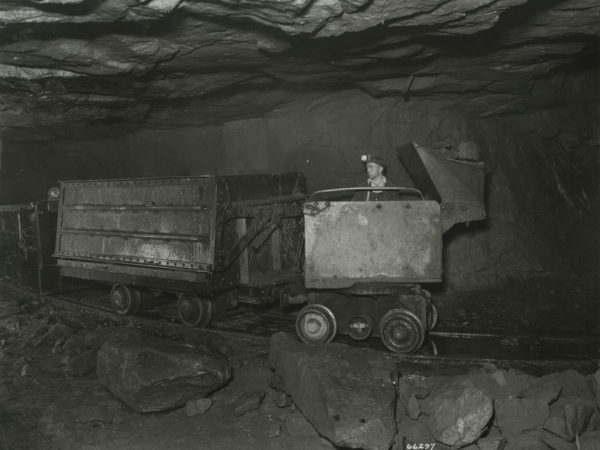 Miner operates an Elmco loader to fill ore car at the Republic Steel Company mine in Mineville
