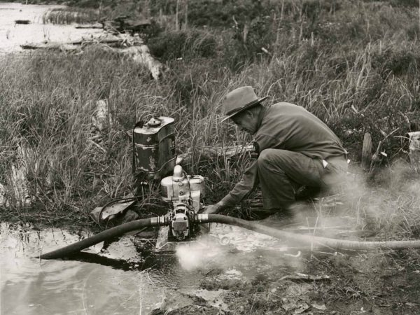 Forest Ranger Franklin Wheeler operates water pump in Warrensburg