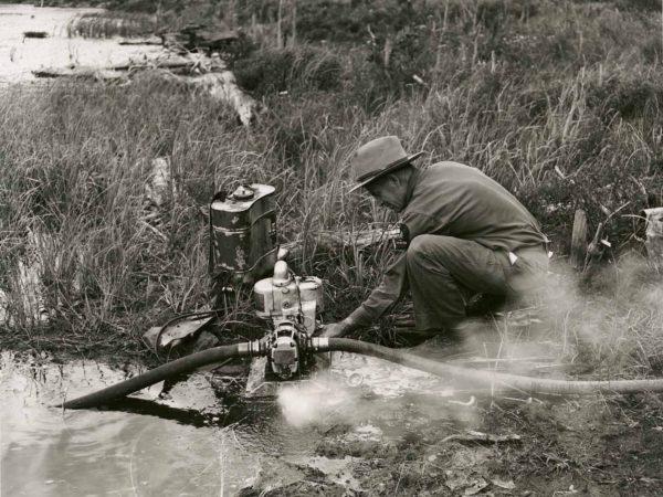 Forest Ranger Franklin Wheeler operates water pump in Warrensburg