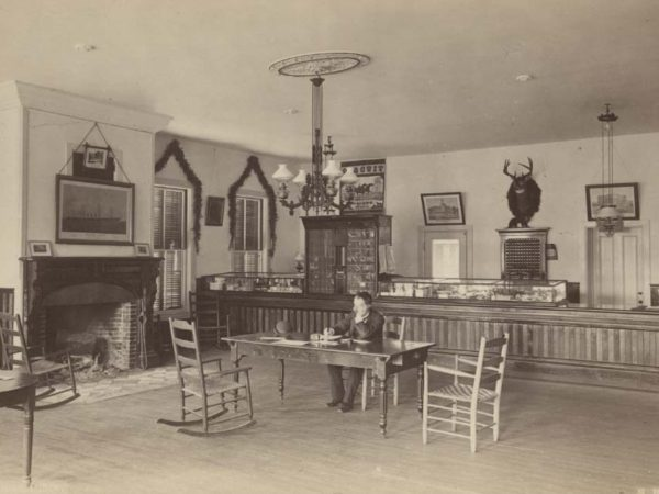 Man at a table in the office of Loon Lake House in Loon Lake