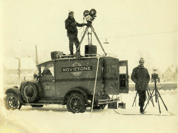 Man operates motion picture camera atop a Fox News truck in Saranac Lake