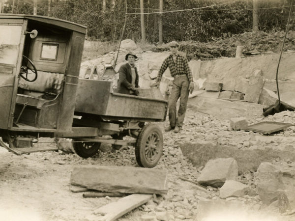 Two men load stone into a truck in the Town of Webb