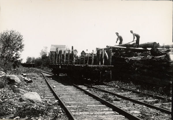 Men load logs onto railroad flatcar in McKeever