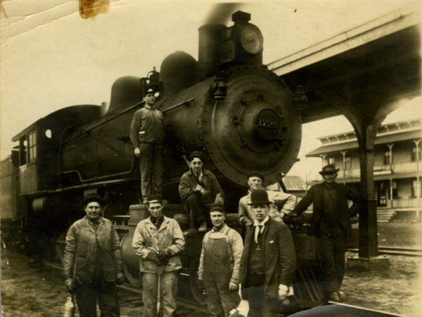 Eight men stand with locomotive at the junction in Lake Clear