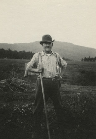 Mr. Wood poses with handtool in his farm field in North Elba