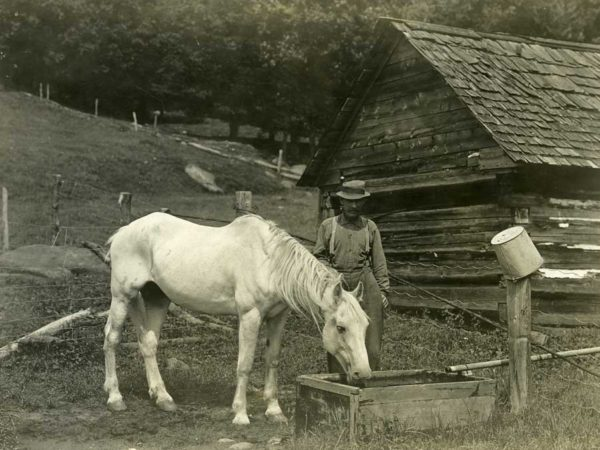 William Schoonmaker with his horse at the watering trough on the Griffin Farm in Indian Lake