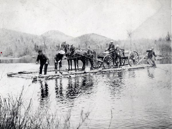 Men ferry a wagon across Cedar River in Indian Lake