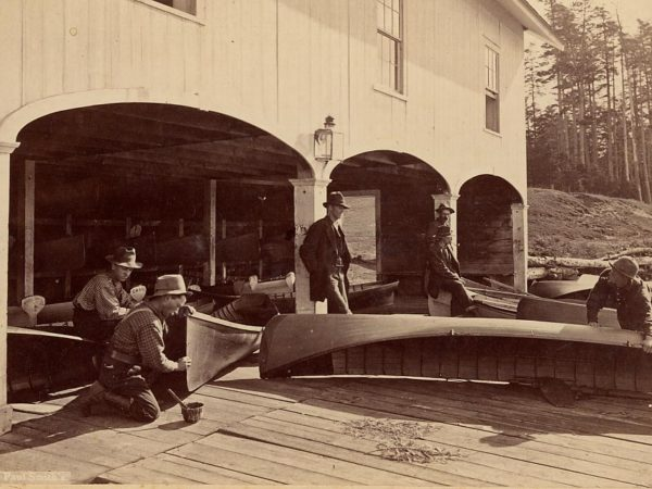 Men with canoes at a boathouse in Paul Smiths