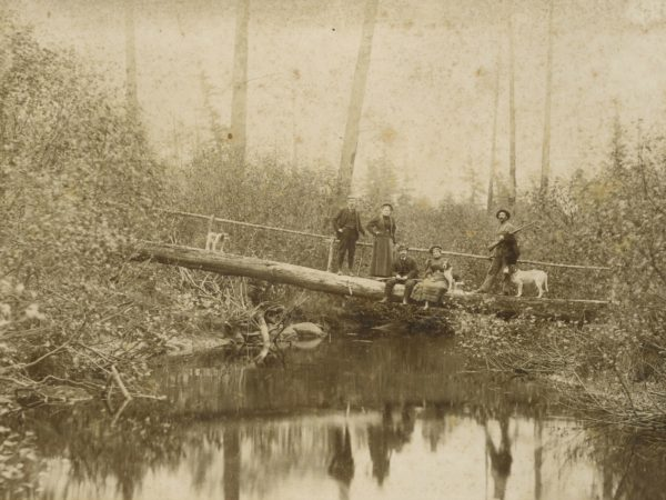 Guides and tourists on a log bridge in Paul Smiths