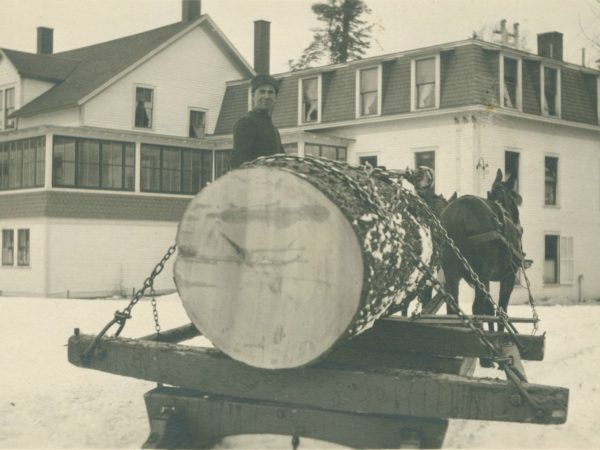 Man with large log on bob sled at Paul Smith's Hotel in Paul Smiths