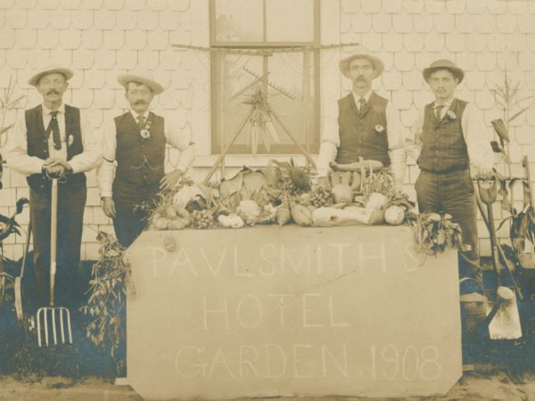 Men with a table of vegetables from the garden at Paul Smith's Hotel in Paul Smiths