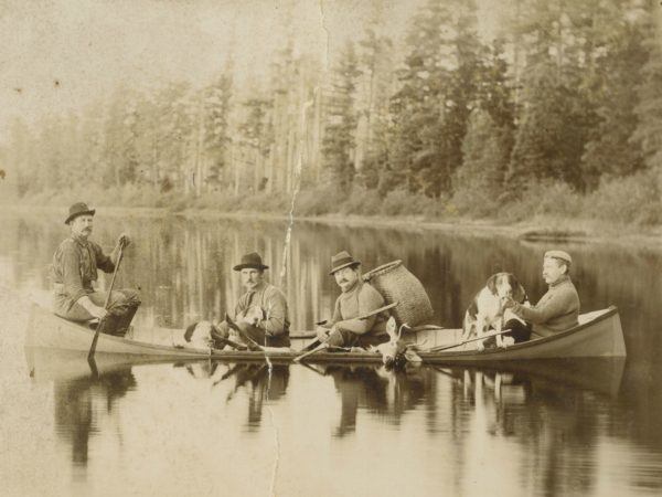 Guides with dogs and deer in a guideboat in Paul Smiths