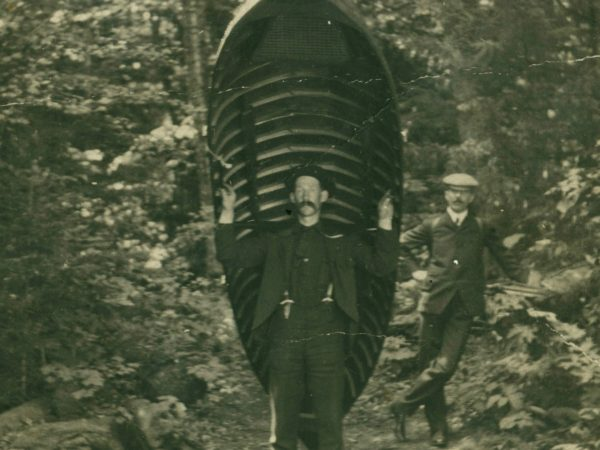 Guide carries a boat through the woods in the Adirondacks