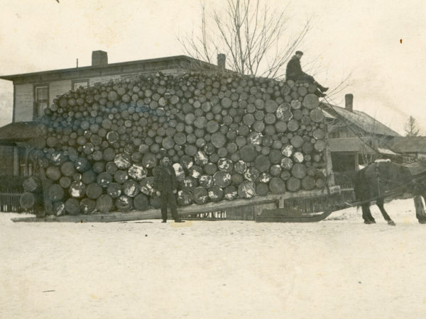 A large load of pulpwood in front of the Spread Eagle Inn in Keene Valley