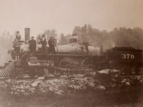 Railroad workers atop an engine in North Creek