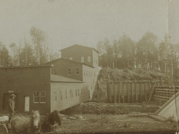 Man on a horse-driven wagon outside the graphite mill in Johnsburg