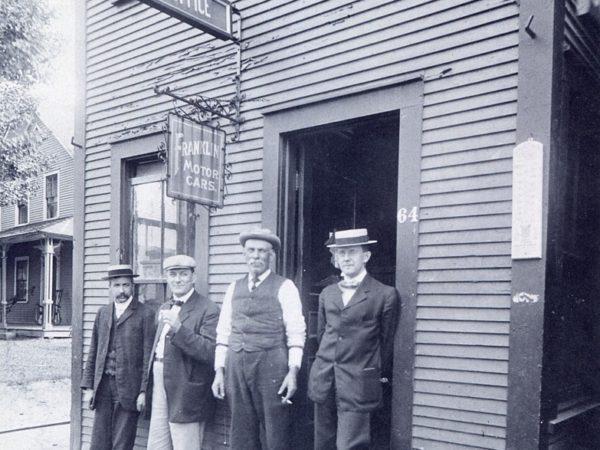 Four men outside Green's Market in Saranac Lake