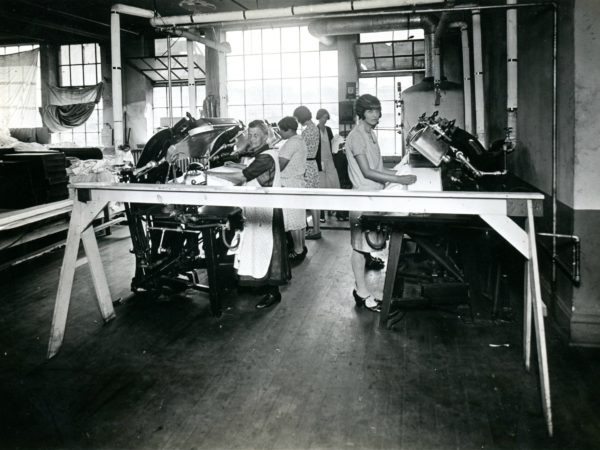 Workers using machines at the Geo Sweetser & Son Shirt Factory in Watertown