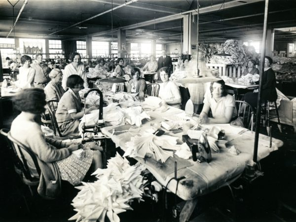 Workers among piles of shirts at the Geo Sweetser & Son Shirt Factory in Watertown