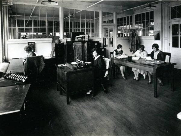 Women doing office work at the Geo Sweetser & Son Shirt Factory in Watertown