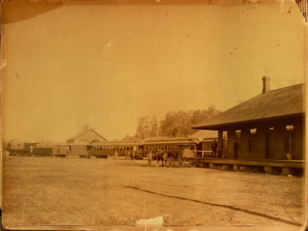 Horse-drawn wagons bearing caskets to the train station