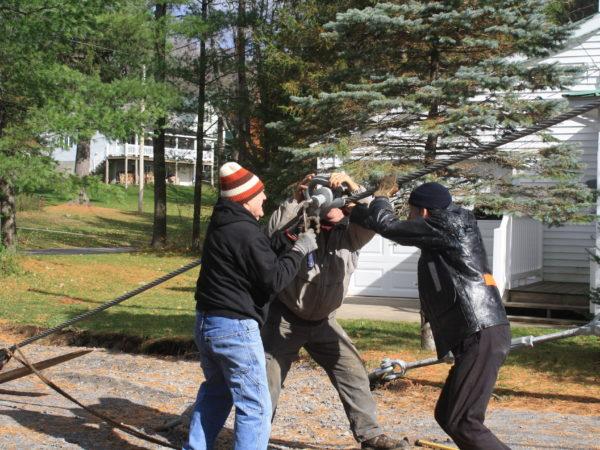 Three men stringing cable for the Wanakena footbridge