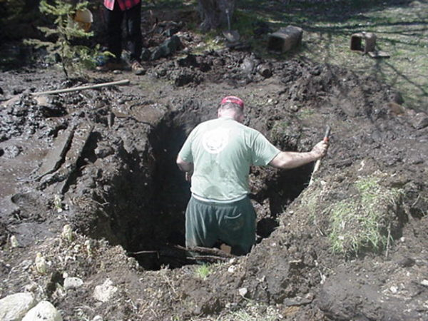 Volunteer fixing a break in the water system in Wanakena