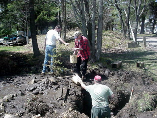 Three volunteers fix a break in the water system in Wanakena