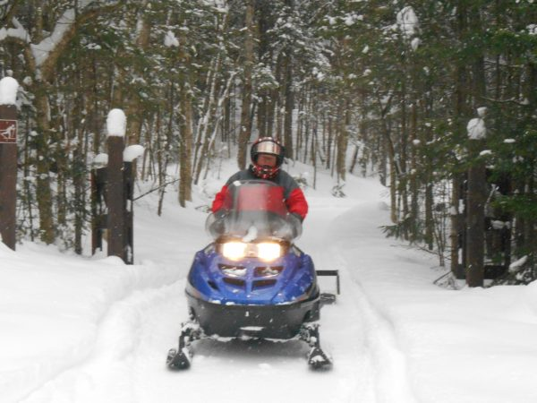 Grooming trails with a snowmobile at Catamount Forest in Colton