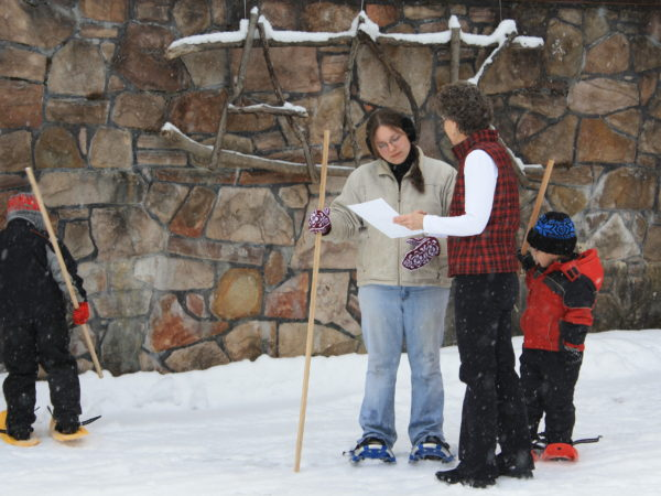 Ruth McWiliams teaching a family to snowshoe in Colton