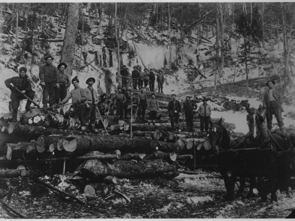 A group of lumberjacks with logs in Tupper Lake