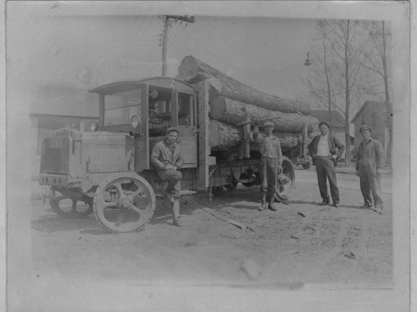 Workers with a Brockway log truck in Tupper Lake
