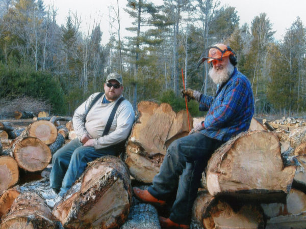 Philip N. Jackson IV, right, and Jack Pulsifer sit on a pile of large, soft maple logs. They were cut close to the Boquet River. Spring 2016. Elizabethtown, NY. Courtesy of Phil Jackson.