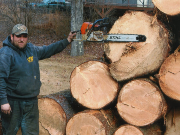 Holding up a chainsaw to a stack of logs in Elizabethtown