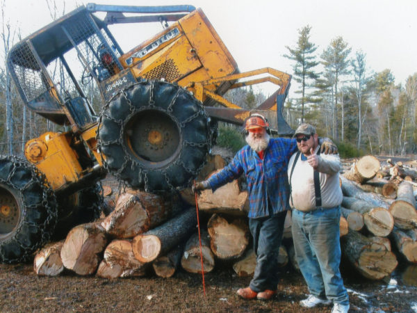 Two lumberjacks posing next to a pile of logs in Elizabethtown